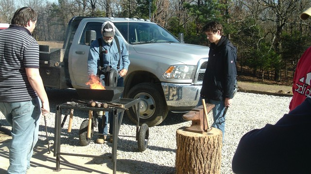 Brad Ussery and Spyro Spanos look on as Larry Ford cranks up the fire in his home made forge.