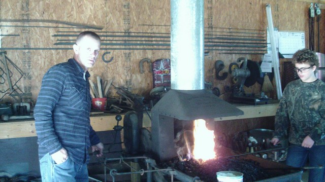 Bryan Carter cranking the forge for his son Kade Carter.